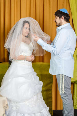 During the chuppah ceremony at a synagogue wedding, the groom covers the bride with a veil in the Badeken ceremony.