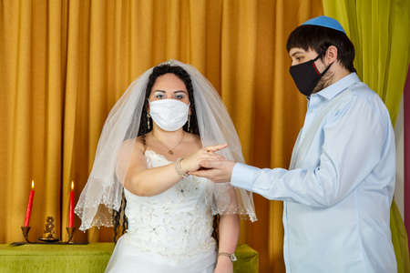 During a chuppah ceremony at a Jewish wedding in a synagogue, the groom puts a ring on the brides index finger of a masked newlywed couple.