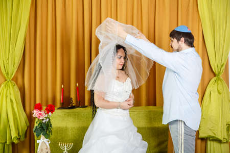 During the chuppah ceremony at a synagogue wedding, the groom lifts the veil from the brides face.