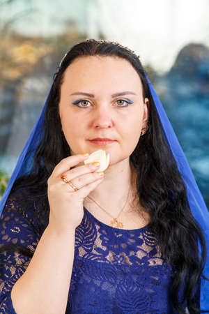 A Jewish woman with her head covered in a blue cape at the Passover Seder table performs the commandment karpas with a bow. Vertical photo