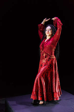 Gypsy woman with long black hair dances with arms with sleeves in a red dress on a black background. Vertical photo
