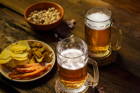 Two mugs with foamy beer and pistachios with chips on a wooden table. Horizontal photo