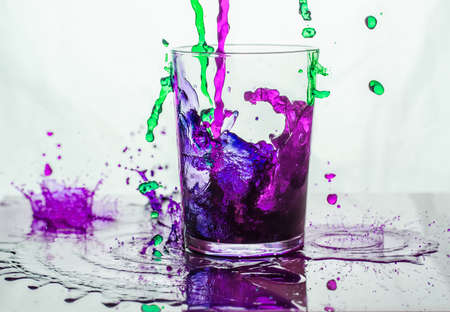 Green and purple liquid spilling into and outside a glass standing on a glass floor.