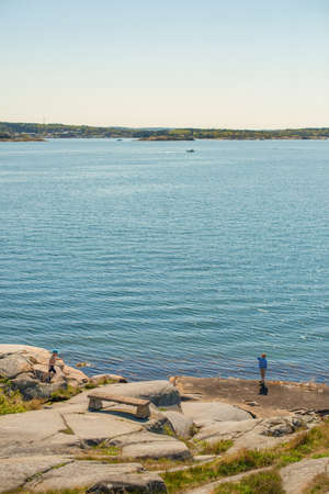 Children playing on the sunny cliffs of Näset Gothenburg.