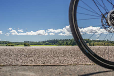 Bicycle wheel on a road in front of an open landscape.