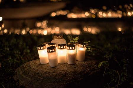 zapalone świece na kamieniu na cmentarzu