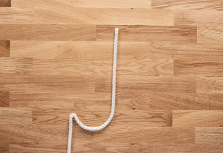 The letter J formed with white rope on a wooden table