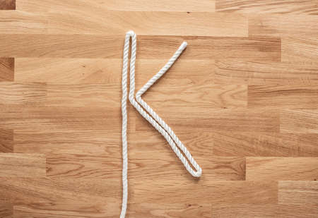 The letter K formed with white rope on a wooden table