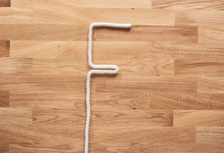 The letter F formed with white rope on a wooden table Фото со стока