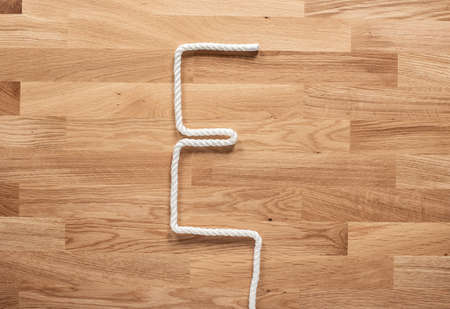 The letter E formed with white rope on a wooden table