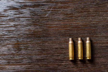 Empty bullet casings on a dark, wooden table.