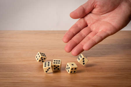 Hand throwing dice in front of a dark background.