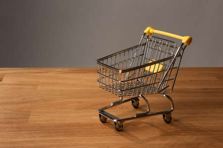 An empty shopping cart on wooden floor in front of a dark grey background. 免版税图像