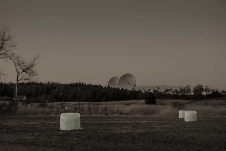 Dystopian view of large satelite dishes behind a forest and fields.