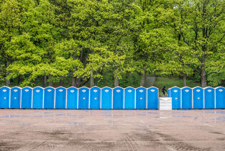 Long row of portable toilets in front of a forest where one has tipped over.