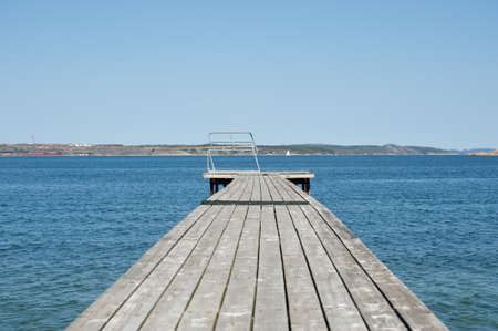 Wooden pier with a spring board waiting for the summer to arrive. Standard-Bild