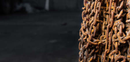 Unused and rusty snow chains hanging from a wall. Standard-Bild