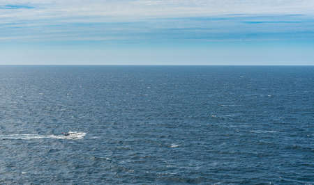 A white cabin cruiser crossing open seas.