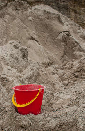 Red plastic bucket in a big pile of sand. Imagens