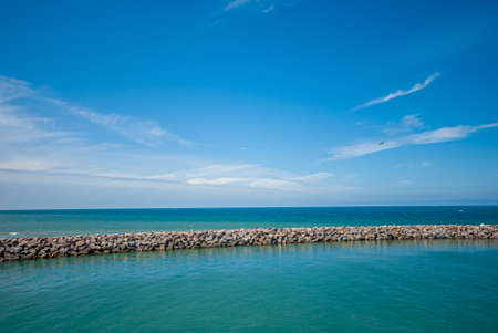 Wellenbrecher mit ruhigem Wasser innen und rauer See außen. Standard-Bild