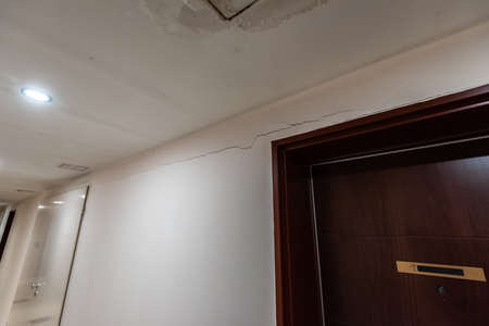 Cracks in a wall by a door.