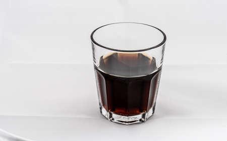 Dark brown drink in a glass on white background.
