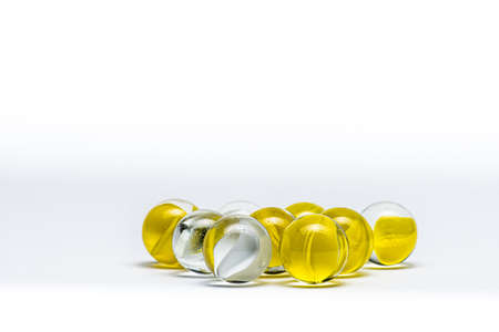 Yellow and white glass marbles on a table. Banco de Imagens