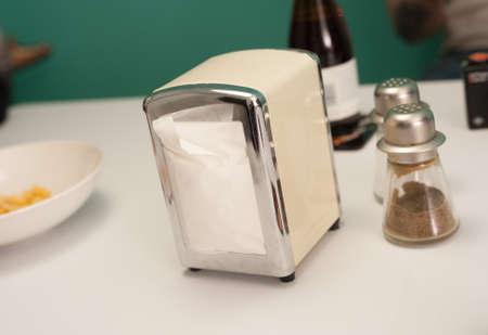 White, metal retro napkin dispenser, Salt and pepper shakers on a table. Stock Photo