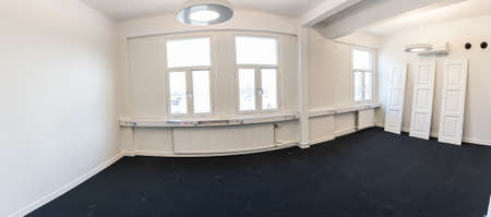 Wide angle image of a white, empty office with black floor and three windows.