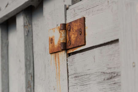 An old, rusty hinge on a white wooden door.