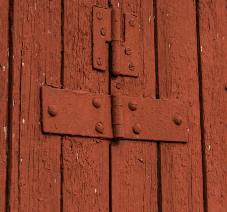 Hinges on a red barn door.