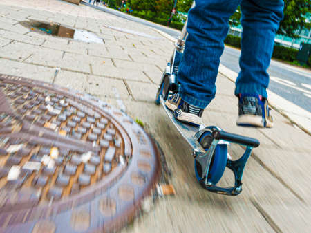 Person on a kickbike passing a rusty manhole cover.