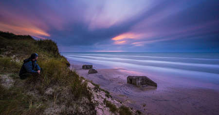 Long exposure of old bunker fortifications on a sandy beach.