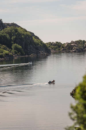 Two small boats on the way out a fjord to fish on the open sea. Stock Photo
