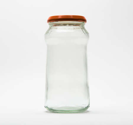 Empty glass jar with an orange lid on white background. Stock Photo