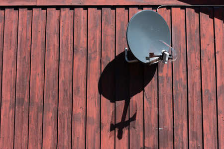 Parabolic antenna on an old wooden wall.