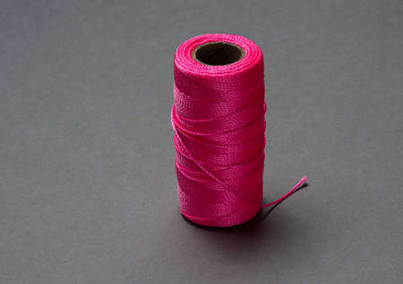 A roll of pink string on grey background. Stock Photo