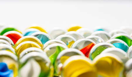 Yellow, green, blue and red glass marbles on a table.
