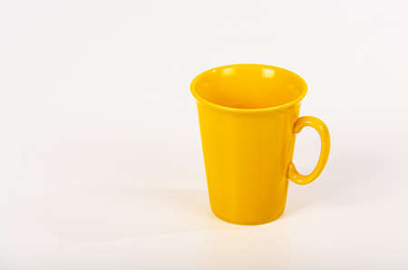 Yellow, right-handed coffee mug on white background.