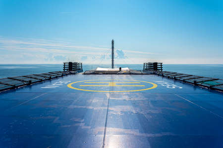 Helideck on top of a ferry at sea. Blue with yellow markings.