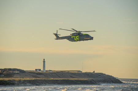 Hirtshals , Denmark - December 28 2009: AgustaWestland AW101, EH101 Merlin, Danish SAR helicopter in action outside Hirtshals harbour. Editorial