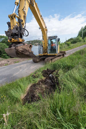 Ramsland, Norway - 20 June 2017: A New Holland excavator digging a ditch