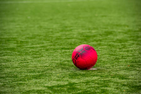 Red football on a green football field..