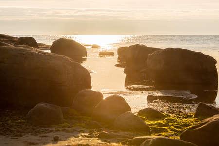 Sunset over rocks by a beach Фото со стока