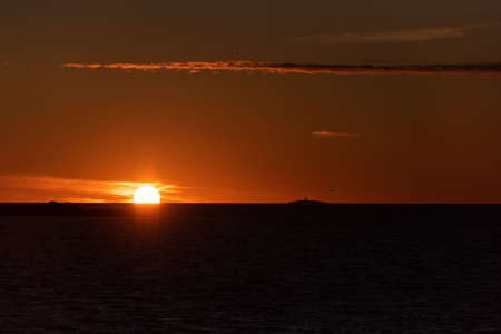 The sun setting in the ocean with small islands and a lighthouse in the horizon