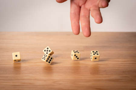 Hand throwing five dice on a wooden table. Stock Photo