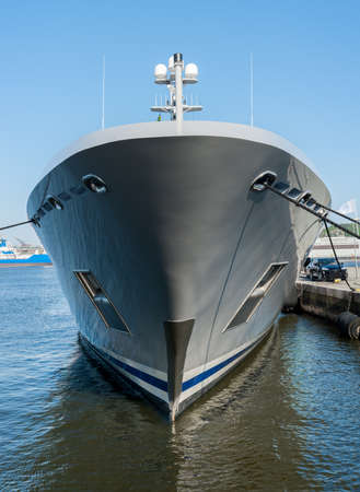 The bow of a grey yacht at port.