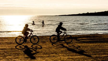 Varberg, Sweden - July 17 2020: Two kids biking on a beach at sunset 新闻类图片