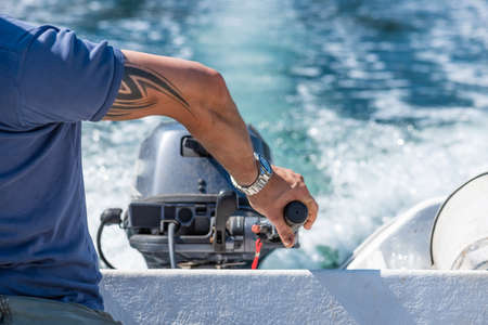 Göteborg, Sweden - July 23 2019: A hand steering an outboard engine on a white plastic boat.