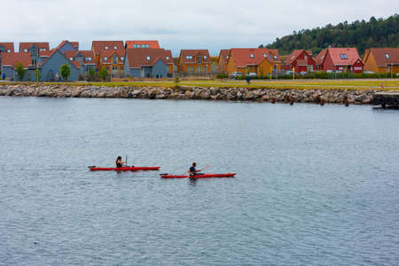 Göteborg, Sweden - July 21 2019: Two persons kayaking by some houses. 新闻类图片